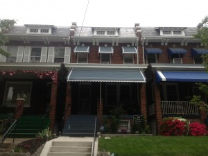 Gray aluminum awning and window hoods in a rowhouse